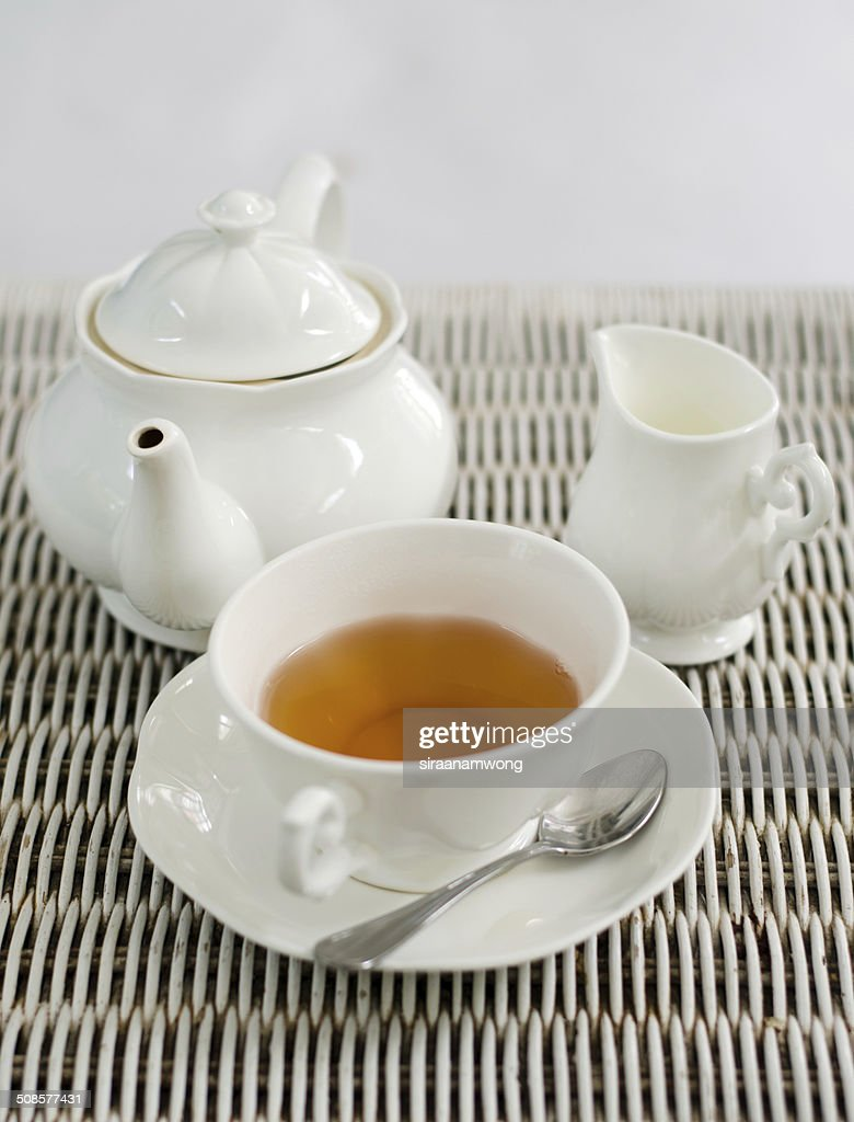 Cup of tea with little milk jar and teapot : Stockfoto