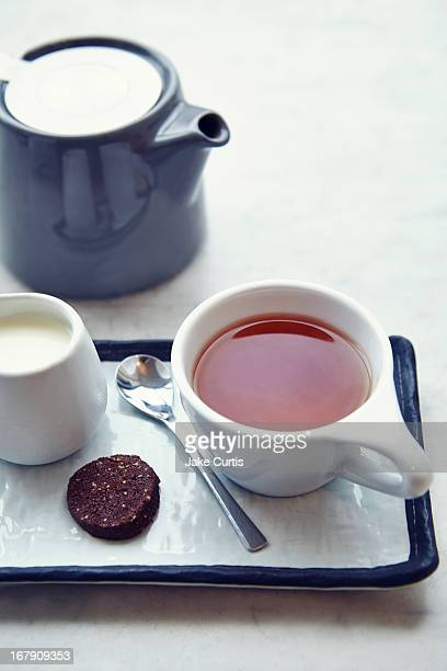 Cup of tea with milk and biscuit on tray