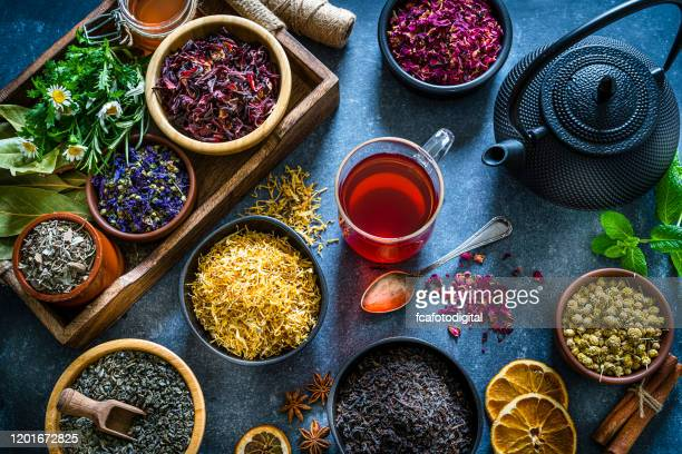 cup of tea with several multi colored dried tea leaves and flowers shot from above on blue table - herbal tea stock pictures, royalty-free photos & images