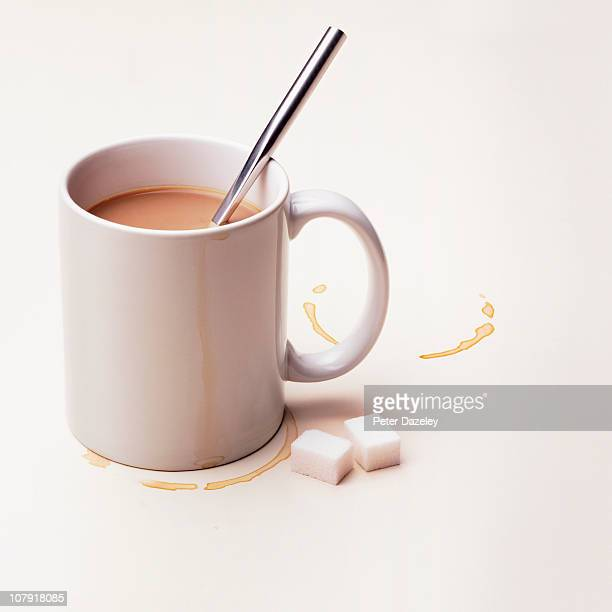 Cup of tea with sugar lumps on white background