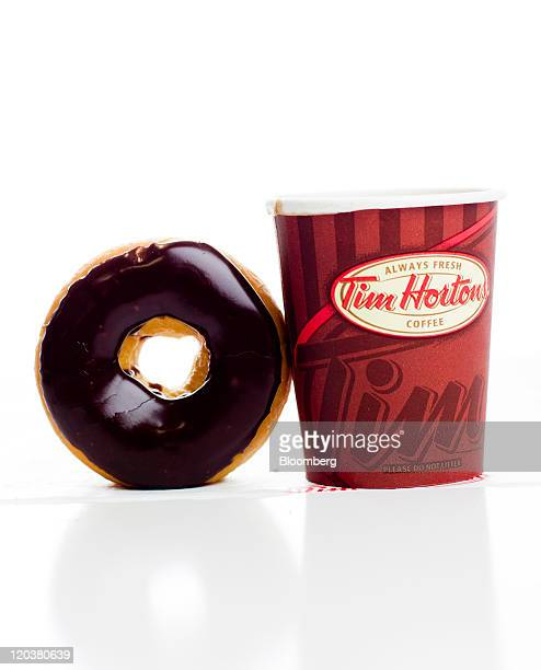 A cup of Tim Hortons Inc coffee and doughnut are arranged for a photograph in Toronto Ontario Canada on Wednesday Aug 3 2011 Tim Hortons Inc is a...