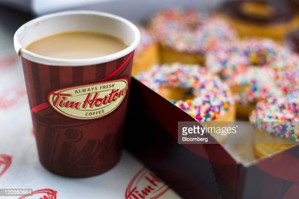 A cup of Tim Hortons Inc coffee and doughnuts are arranged for a photograph in Toronto Ontario Canada on Wednesday Aug 3 2011 Tim Hortons Inc is a...