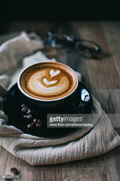 A cup of well-made cappuccino in a black coffee cup set with roasted beans