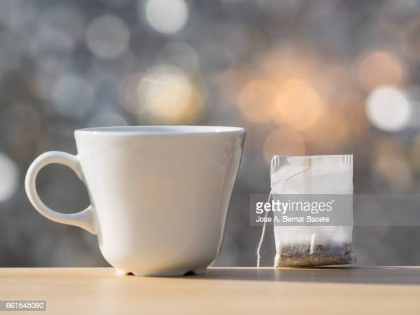cup on a table to prepare an infusion of grasses of tea (tea bag ),  illuminated by the light of the sun - refresco stock photos and pictures