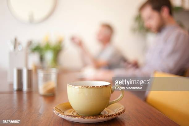 Cup on table and people in background in a cafe