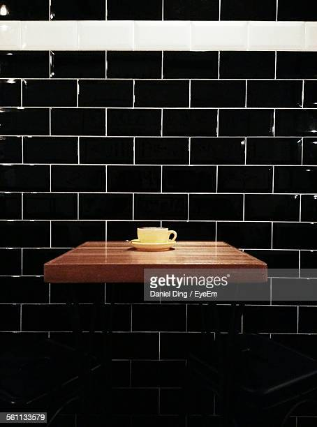 Cup On Table By Tiled Wall