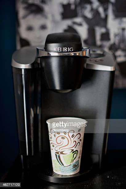 Cup sits in a Keurig Green Mountain Inc. Coffee machine in this arranged photograph taken at a salon in Princeton, Illinois, U.S., on Tuesday, Feb....