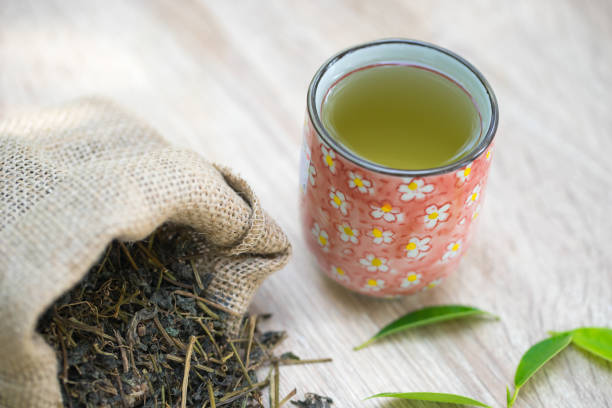 Cup with green tea on wooden background