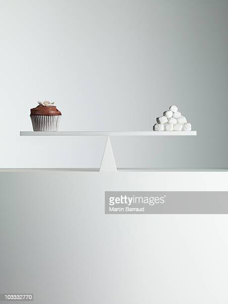Cupcake and stack of sugar cubes balanced on seesaw