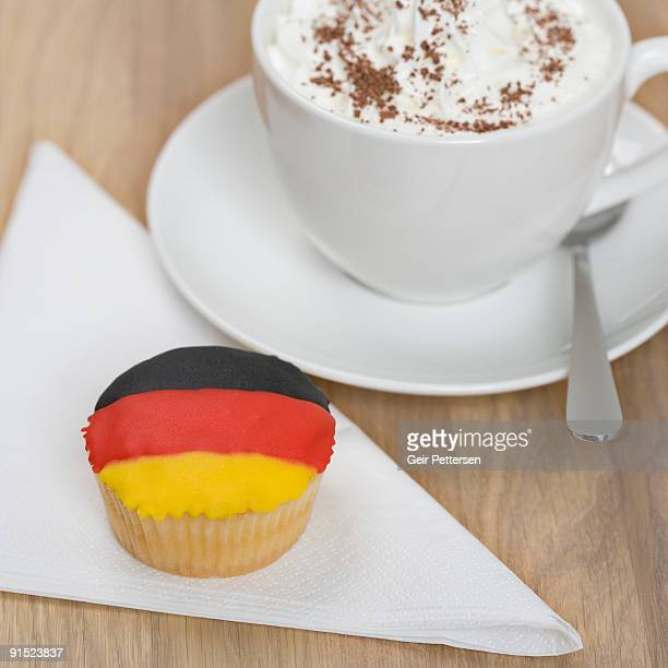 Cupcake decorated with flag and cup of hot drink