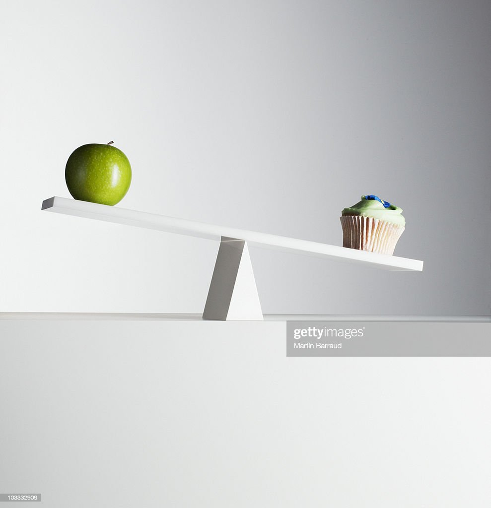Cupcake tipping seesaw with green apple on opposite end : Stock Photo