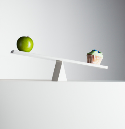 Cupcake tipping seesaw with green apple on opposite end - gettyimageskorea
