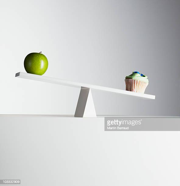 Cupcake tipping seesaw with green apple on opposite end