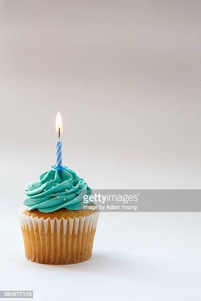 Cupcake with blue icing and one candle