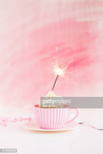 Cupcake with buttercream frosting in a teacup with a sparkler