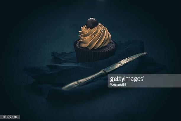 cupcake with chocolate cream in front of dark background - チョコレートチップマフィン ストックフォトと画像