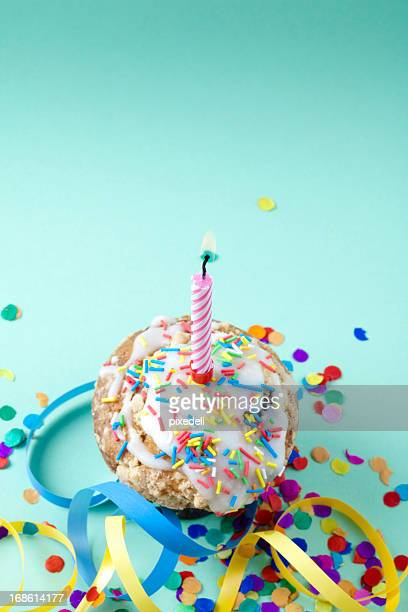 Cupcake with lit candle and confetti