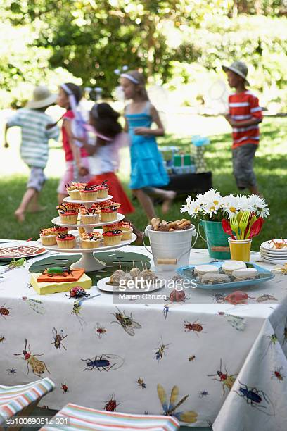 Cupcakes and desserts on table, children (6-11) playing in background