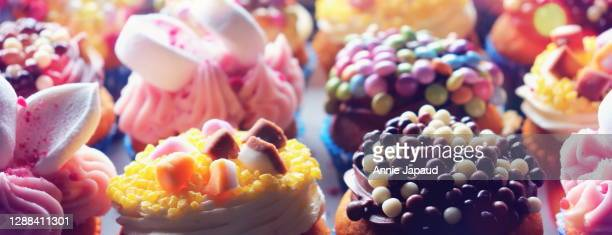 cupcakes header image closeup with many sweets and colours, soft dreamy light - bakery stock pictures, royalty-free photos & images