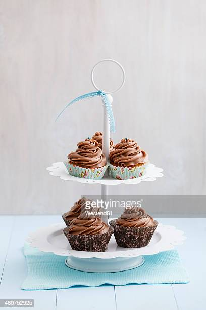 Cupcakes topped with chocolate buttercream on cake stand, close up