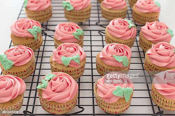 Cupcakes with pink buttercream on a cooling rack
