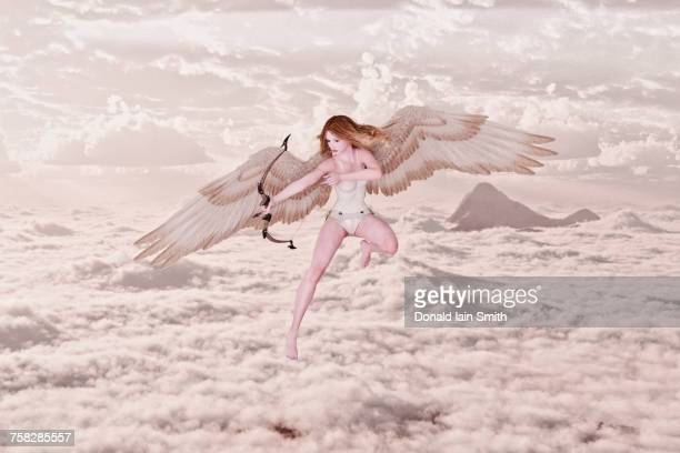 cupid angel shooting bow and arrow in clouds - cupido foto e immagini stock