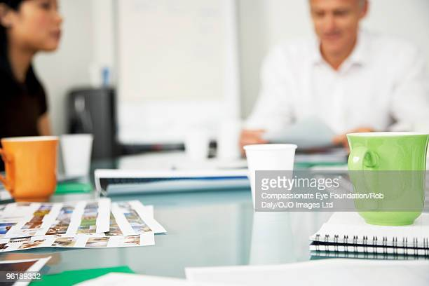 cups and papers on conference room table - compassionate eye foundation stock pictures, royalty-free photos & images