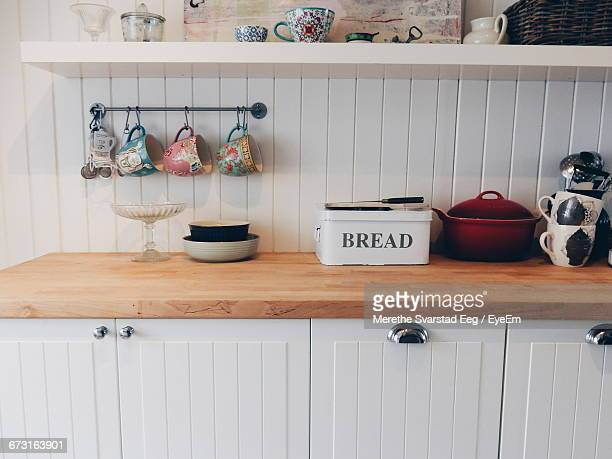 cups hanging by containers on kitchen counter - pianale da cucina foto e immagini stock