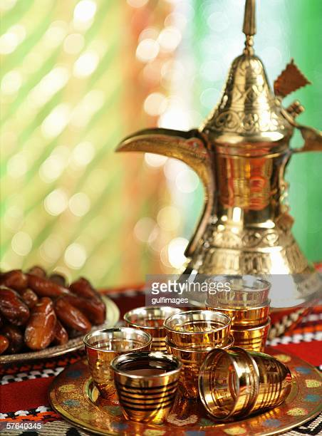 Cups of coffee and dates in a tray.