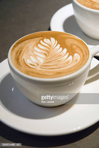 Cups of coffee on counter, leaf draw on foam