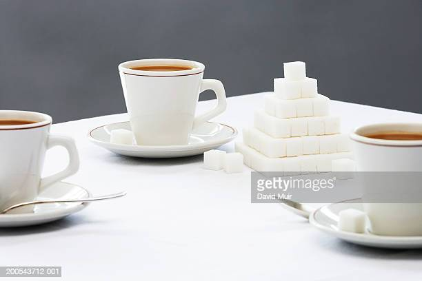 Cups of coffee on table, with sugar cubes stacked in pyramid shape