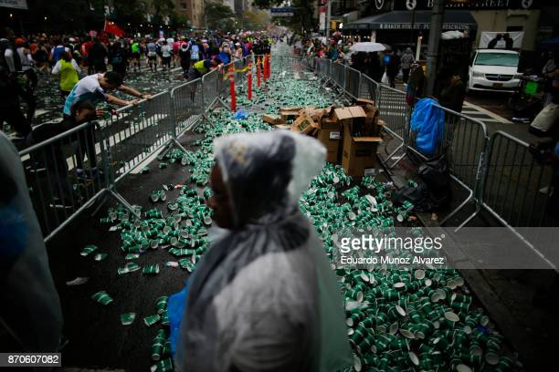 Cups used for hydration are seen on the ground of 1st Ave as runners make their way in Manhattan during 2017 TCS New York City Marathon November 5...