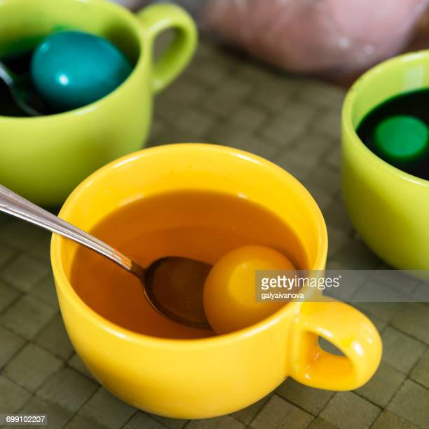Cups with eggs and colored dye for Easter