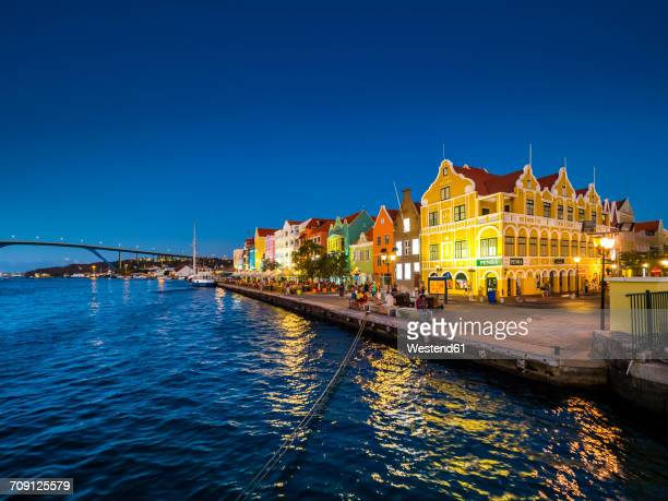 Curacao, Willemstad, Punda, colorful houses at waterfront promenade in the evening