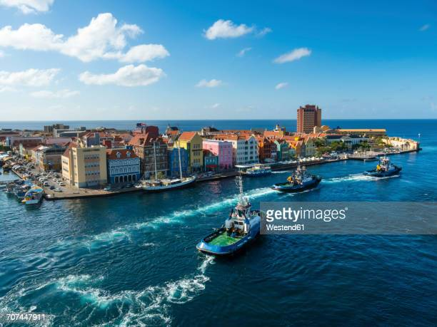 curacao, willemstad, punda, tugboats and colorful houses at waterfront promenade - curaçao stockfoto's en -beelden