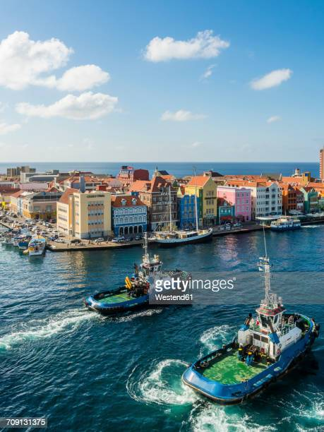 Curacao, Willemstad, Punda, tugboats and colorful houses at waterfront promenade