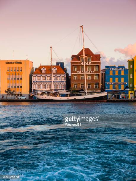 Curacao, Willemstad, schooner and colorful houses at waterfront promenade