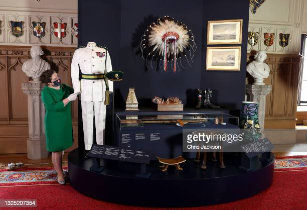 Curator adjusts a display of items at an exhibition that commemorates the life and work of HRH Prince Philip, Duke of Edinburgh in the Great Hall at...