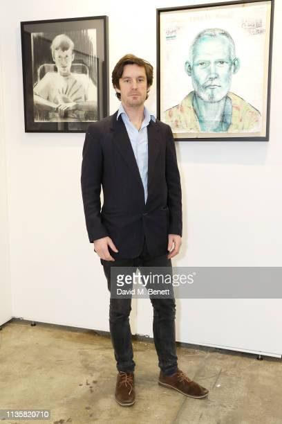 Curator Ben Moore poses with portraits from the Unmissable25 exhibition during the private view of The Other Art Fair at The Old Truman Brewery on...