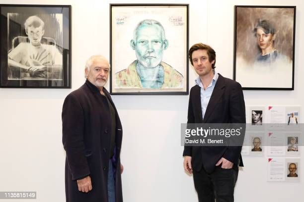 Curator Ben Moore with Artist Ricardo Cinalli pose with his portrait from the Unmissable25 exhibition during the private view of The Other Art Fair...