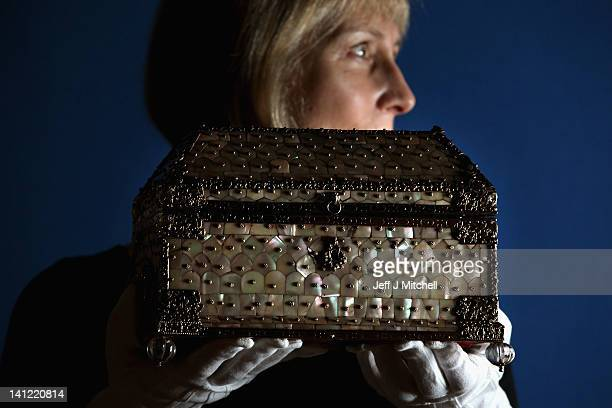 Curator Deborah Clarke holds a casket presented to Queen Elizabeth the Queen Mother in 1938 part of the Royal Collection on display at the Queens...
