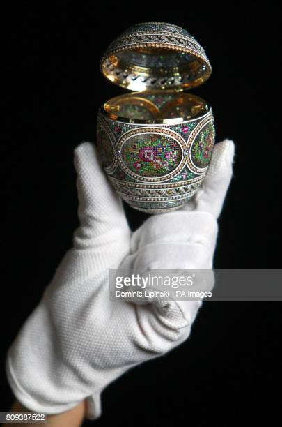 A curator from the Royal Collection examines a mosaic egg made by Russian jeweller and goldsmith Peter Carl Faberge which was originally commissioned...