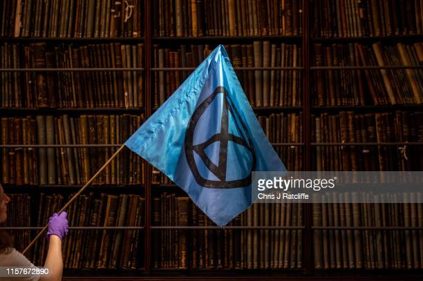 Curator handles an Extinction Rebellion flag in front of book cases at The V&A on July 26, 2019 in London, England. Today a series of new...