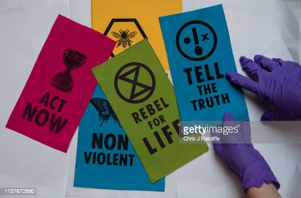Curator handles cloth Extinction Rebellion patches at The V&A on July 26, 2019 in London, England. Today a series of new acquisitions exploring the...