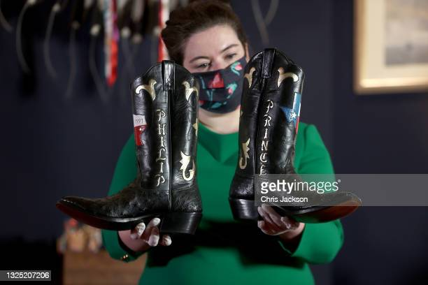 Curator holds a pair of cowboy boots gifted to Prince Philip during a visit to Houston Texas in the Great Hall of Windsor Castle at an exhibition...
