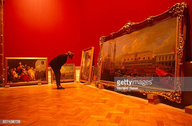 A curator inspects art canvasses leaning against gallery walls in the Royal Academy for its 'The Glory of Venice Art in the Eighteenth Century'...