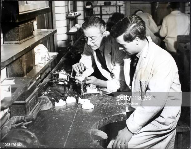 Curator instructing a dental student in dentures or false teeth, in the Prosthetic Department at the Dental School of The University College...