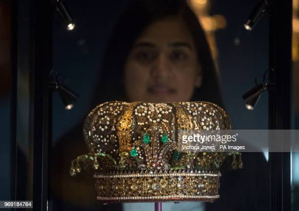 Curator Kajal Meghani looks at a crown commissioned for the Prince of Wales' visit to India in 1876 during the photocall for the new Splendours of...
