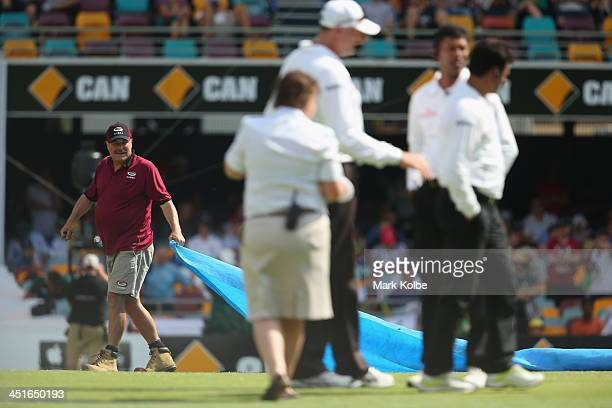 GABBA curator Kevin Mitchell removes the covers as the umpires assess the field during day four of the First Ashes Test match between Australia and...