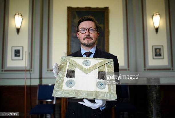 Curator Mark Dennis poses for a photograph with a masonic apron worn by Winston Churchill who was a Master Mason during a press preview for the...